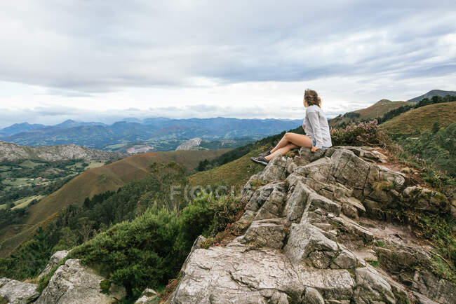 Side view of young faceless female in casual wear sitting on edge of cliff and admiring view of mountain green beautiful range while travelling on summer day in Asturias in Spain — Stock Photo