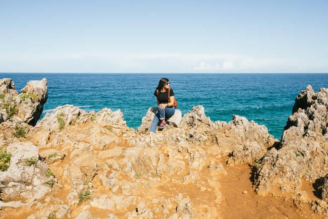 Jeune femme assise sur une falaise près de la mer — Photo de stock