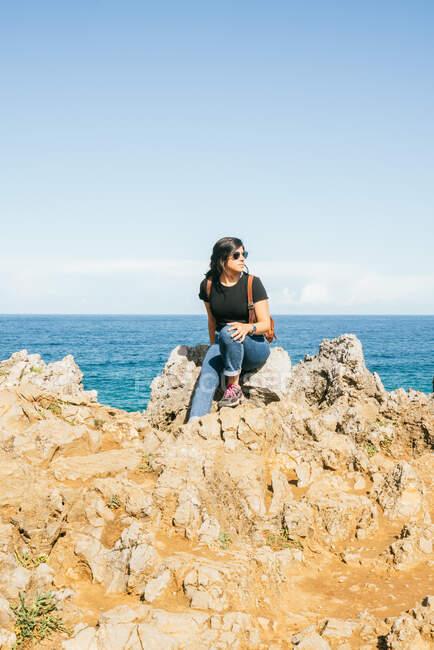 Distance jeune femme en vêtements décontractés et lunettes de soleil assis sur une falaise rocheuse et regardant loin tout en se reposant à côté de la mer bleue contre le ciel nuageux par une journée ensoleillée — Photo de stock