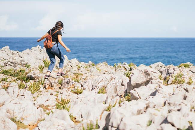 Femme méconnaissable marchant sur une colline dans la nature — Photo de stock