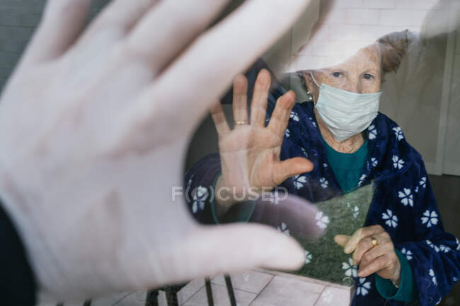 Redhead aged female in medical mask waving hand through window to relative while isolating at home and conducting social distancing during pandemic of coronavirus — Stock Photo