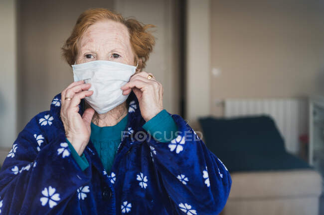 Senior female with red hair in blue robe and medical mask looking at camera while standing in hospital room — Stock Photo
