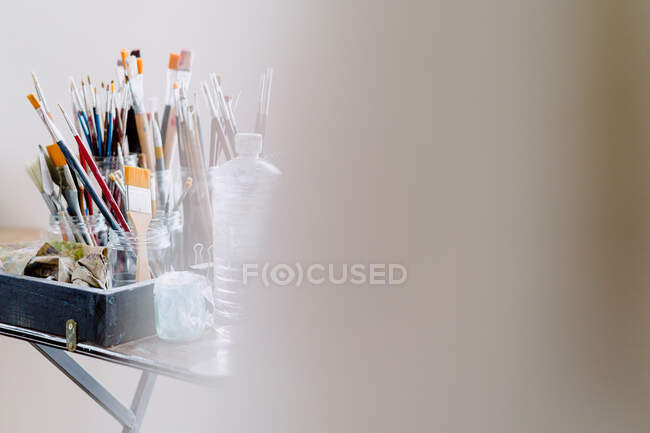 Many various paintbrushes in glass on table — Stock Photo