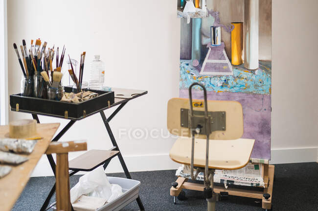 Table with various tools for painting paintbrushes and wooden easel with colorful oil painting in creative modern interior of cozy art workshop — Stock Photo