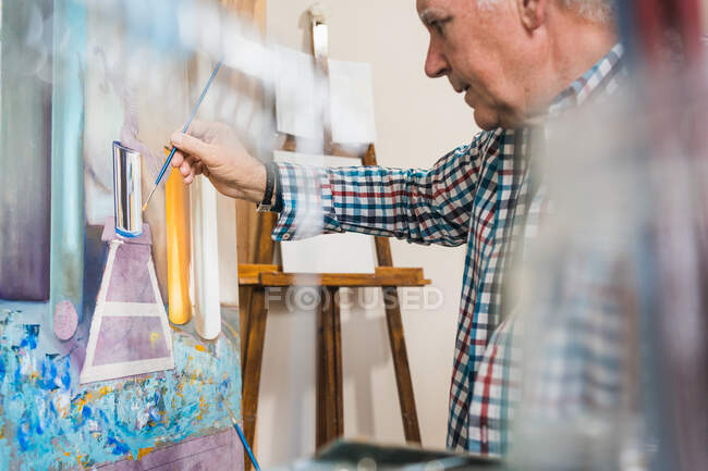 Aged man painting picture with brush — Stock Photo