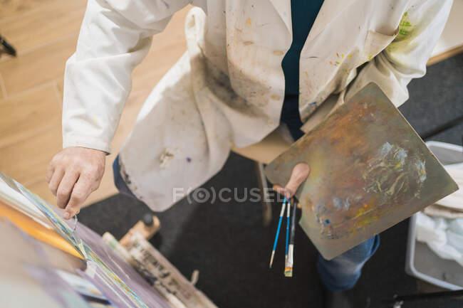 Літній чоловік малює пензлем. — стокове фото