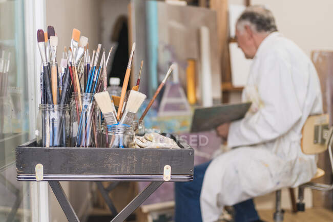 Many paintbrushes in glass on table — Stock Photo
