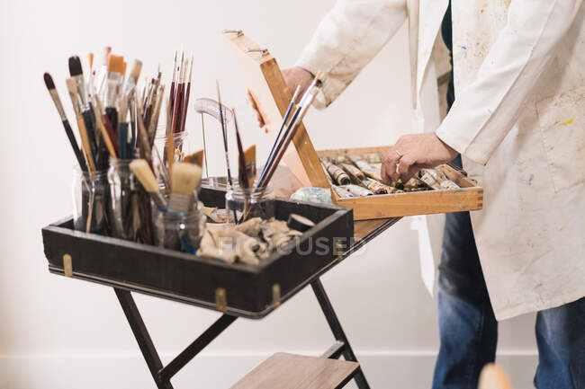 Senior artist standing in home workshop and choosing paints — Stock Photo