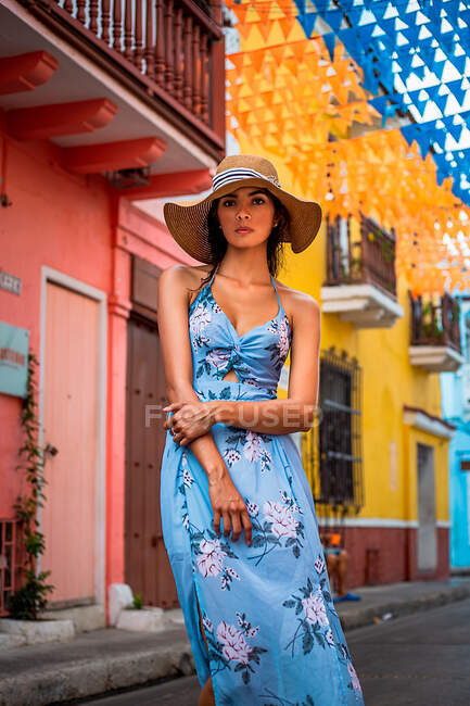 Calm young female in stylish blue summer dress and hat looking at camera while standing near aged building with colorful walls on city street — Stock Photo