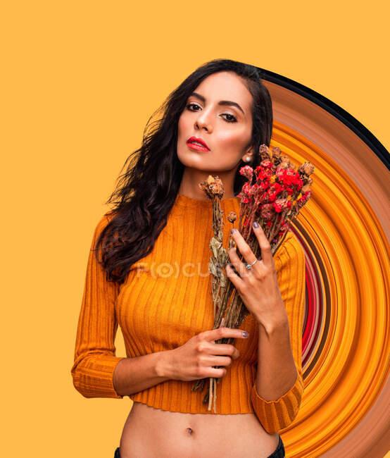 Fiducioso giovane modello femminile in top crop arancio alla moda con mazzo di fiori freschi e guardando la fotocamera mentre in piedi contro la parete arancione brillante con ornamento geometrico in studio — Foto stock