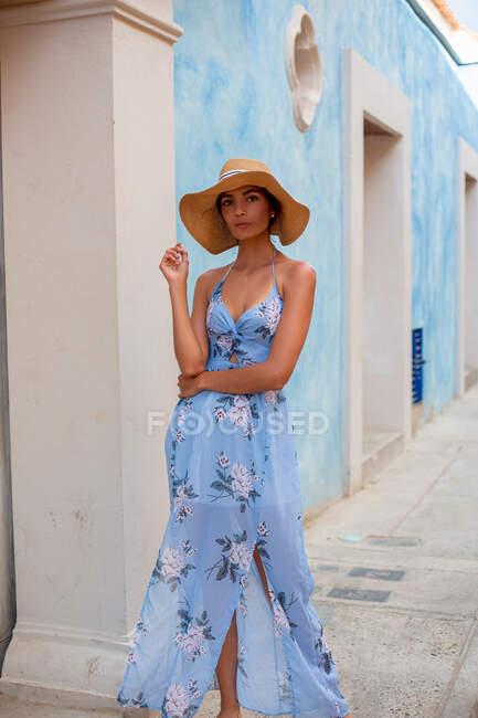 Hermosa joven hembra en hermoso vestido de sol y sombrero de paja mirando a la cámara mientras está de pie cerca del edificio envejecido con paredes azules en la calle - foto de stock