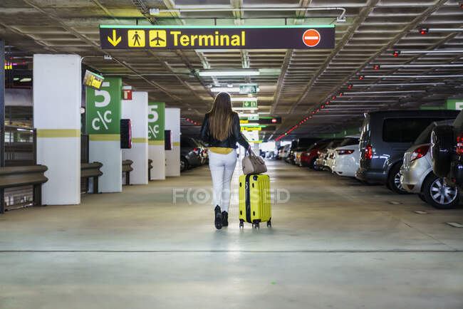 Teenager in casual clothes with long hair walking in parking and carrying yellow suitcase in airport building — Stock Photo
