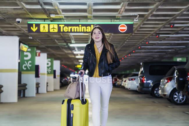 Jóvenes positivos acaban de llegar adolescentes vestidos con ropa casual, con largos pelos paseando en el aparcamiento y llevando maleta amarilla en el edificio del aeropuerto. - foto de stock