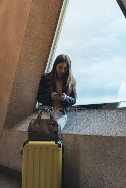 Adolescent en vêtements décontractés avec valise et sac debout près de la fenêtre appuyé sur le mur et parlant sur smartphone à l'aéroport — Photo de stock