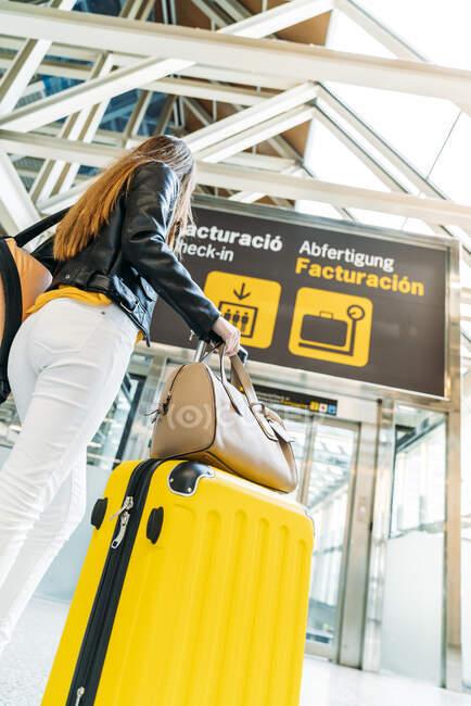 Adolescent en casquette jaune veste en cuir noir et chemisier jaune debout avec valise dans le terminal de l'aéroport moderne et regardant la caméra — Photo de stock