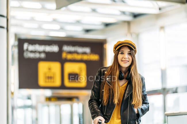 Adolescent souriant élégant en casquette jaune veste en cuir noir et chemisier jaune avec écouteurs debout avec valise dans l'aérogare moderne et regardant la caméra — Photo de stock