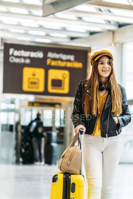 Adolescente sorridente elegante em casaco de couro preto boné amarelo e blusa amarela com fones de ouvido de pé com mala no terminal do aeroporto moderno e olhando para a câmera — Fotografia de Stock