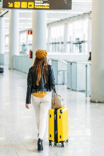 Adolescente em roupa elegante com bagagem e passaporte no bolso traseiro olhando para a câmera e acenando adeus enquanto está ao lado do balcão de check-in no aeroporto — Fotografia de Stock