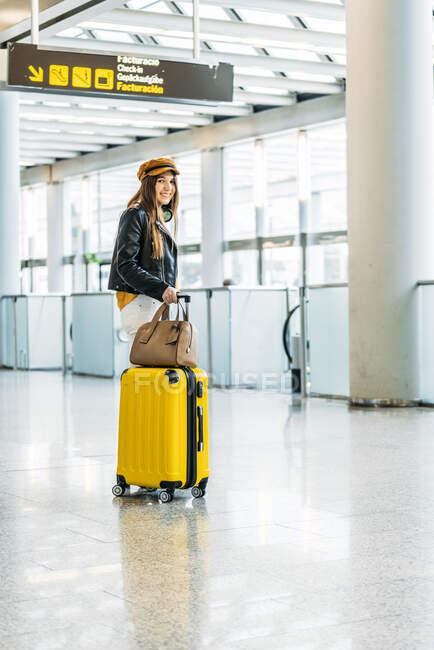 Adolescente in abito alla moda con bagagli e passaporto in tasca posteriore guardando la fotocamera e salutando mentre in piedi accanto al banco check-in in aeroporto — Foto stock