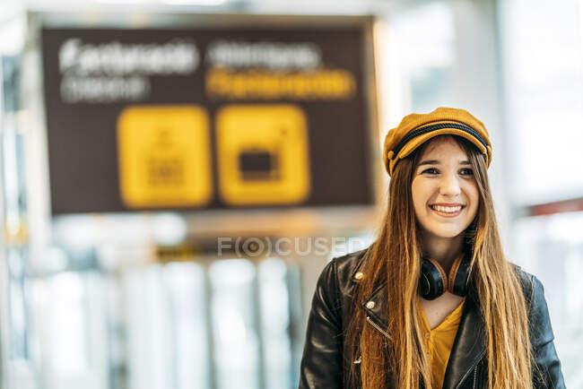 Adolescent en casquette jaune veste en cuir noir et chemisier jaune avec écouteurs debout avec valise dans le terminal de l'aéroport moderne et regardant la caméra — Photo de stock