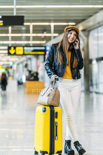 Teenager standing with legs crossed holding luggage and bag and talking on phone cheerfully while waiting for flight at airport terminal — Stock Photo