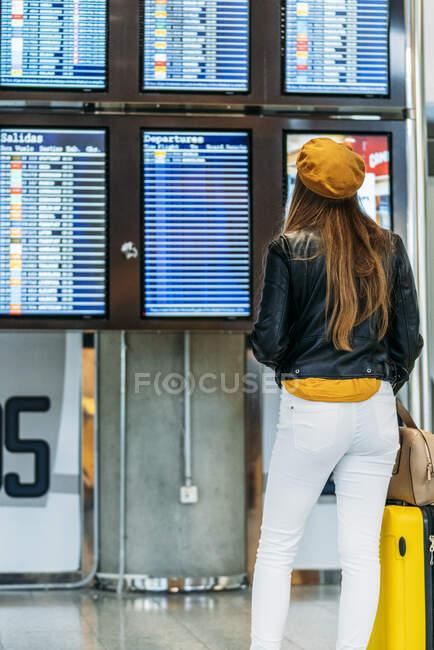 Vista posteriore dell'adolescente in abito alla moda con bagaglio in piedi vicino all'orario e controllo dell'orario di partenza sul display digitale in attesa del volo al terminal dell'aeroporto — Foto stock