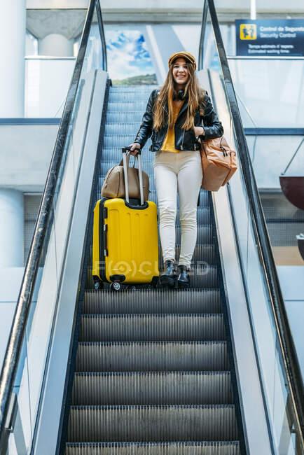 Adolescente con audífonos de pie en escaleras móviles con maleta amarilla y bolsas en mano en la terminal del aeropuerto grande. - foto de stock