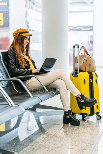 Vista lateral de un adolescente serio con ropa elegante sentado en el banco con las piernas cruzadas con el equipaje y pasar tiempo libre usando el ordenador portátil mientras espera el embarque en el aeropuerto - foto de stock