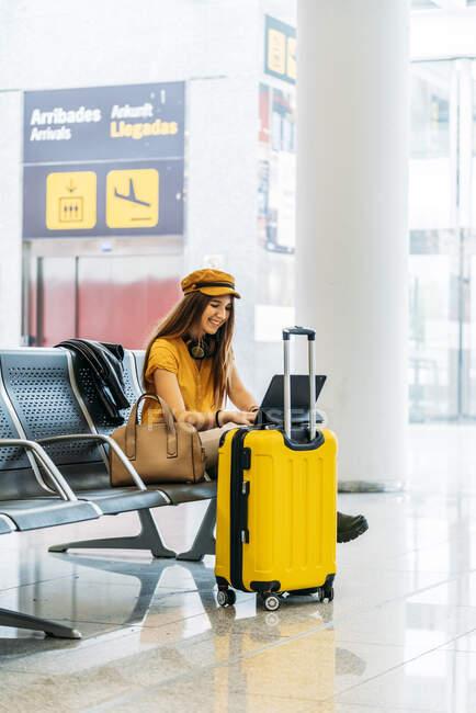 Vista laterale di serio adolescente in abiti eleganti seduto sulla panchina con le gambe incrociate con i bagagli e trascorrere il tempo libero utilizzando il computer portatile in attesa di imbarco in aeroporto — Foto stock