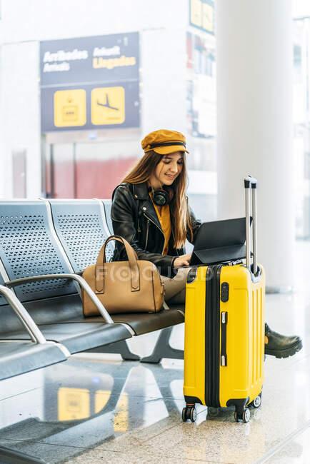Вид сбоку серьезного подростка в стильной одежде, сидящего на скамейке со скрещенными ногами и проводящего свободное время с ноутбуком в ожидании посадки в аэропорту — стоковое фото