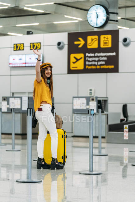 Full length of joyful teenager in fashionable outfit with luggage and passport in back pocket looking at camera and waving goodbye while standing next to check in counter at airport — Stock Photo