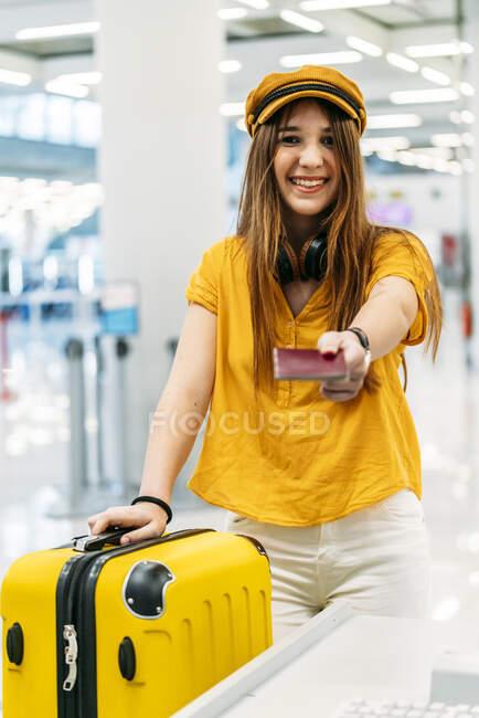 Adolescent souriant joyeux dans des vêtements élégants colorés et écouteurs donnant passeport et regardant la caméra tout en se tenant au comptoir d'enregistrement dans le terminal de l'aéroport — Photo de stock