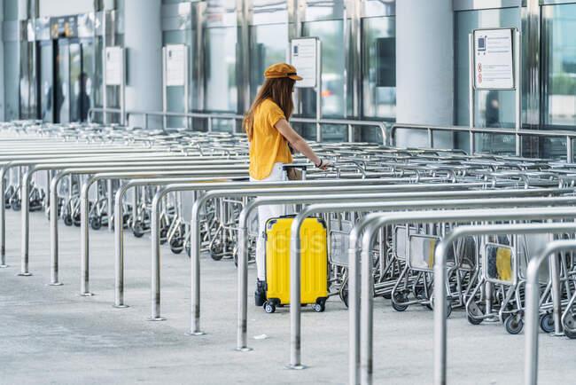 Corpo inteiro de adolescente elegante irreconhecível em roupa colorida com mala de plástico amarelo recebendo carrinho de bagagem enquanto estava perto do edifício do aeroporto — Fotografia de Stock