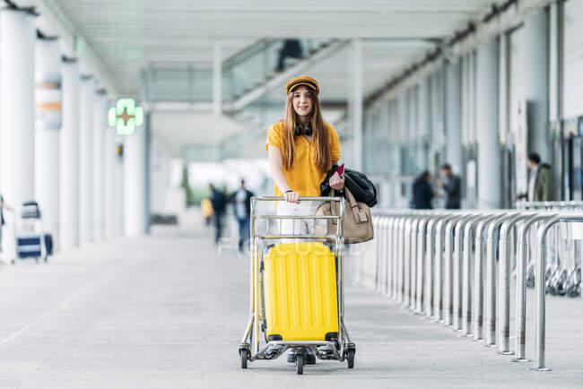 Júnior sonriente en equipamiento casual y audífonos con bolsa de cuero y pasaporte en la mano mirando a la cámara y transportando el carro de equipaje cerca de un moderno edificio del aeropuerto. - foto de stock