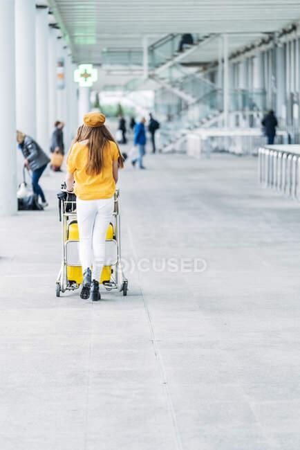 Joven adolescente que conduce el carro de equipaje en el aeropuerto - foto de stock
