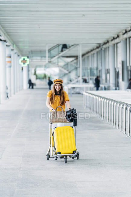 Smiling teenager in casual outfit and headphones with leather jacket bag and passport in hand looking at camera and carrying luggage cart near modern airport building — Stock Photo