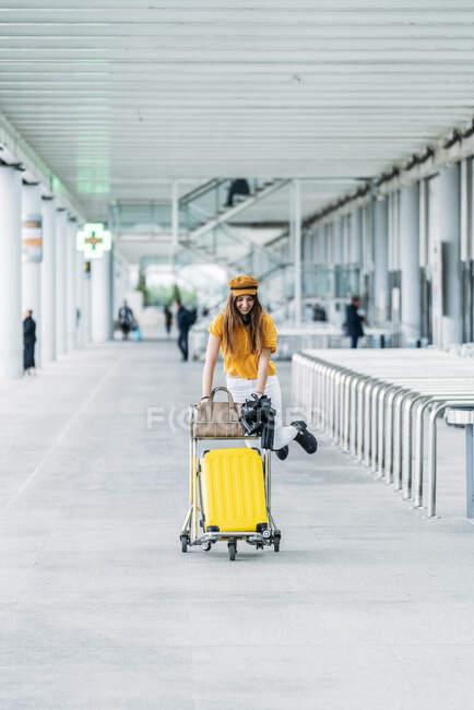 Adolescente sorridente in abbigliamento casual e cuffie con borsa giacca di pelle e passaporto in mano guardando la fotocamera e portando il carrello bagagli vicino al moderno edificio dell'aeroporto — Foto stock