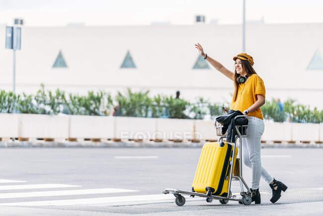 Pleine longueur de joyeux adolescent en casquette jaune avec écouteurs et chariot à bagages complet attraper le taxi tout en se tenant près de la route à l'extérieur du terminal de l'aéroport principal sur la chaude journée d'été — Photo de stock