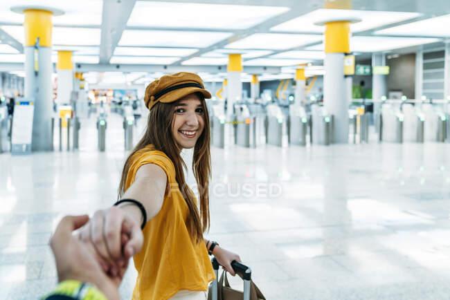 Jóvenes adolescentes sonrientes en un elegante equipo liderando a alguien a mano y mirando la cámara en camino a la sala de espera con maleta en la terminal del aeropuerto. - foto de stock