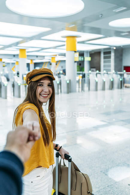 Young smiling teenager in stylish outfit leading someone by hand and looking at camera on way to waiting room with suitcase in airport terminal — Stock Photo
