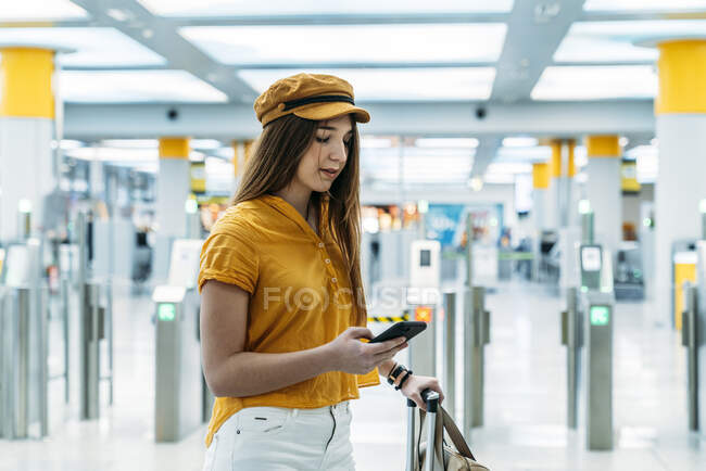 Side view of teenager in stylish outfit and trendy cap holding suitcase in hand and browsing smartphone while standing in airport hall — Stock Photo