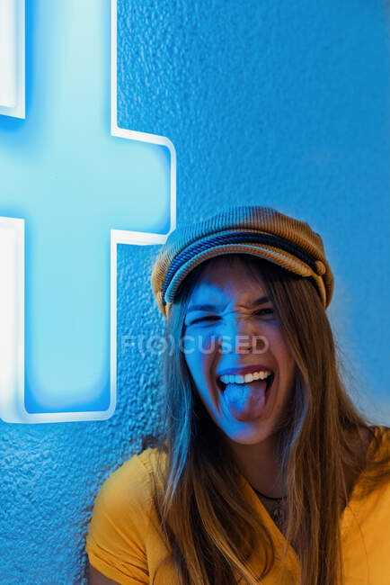 Happy young teenager in yellow t shirt and trendy cap making funny grimace and showing tongue against blue wall with neon sign of medical cross — Stock Photo