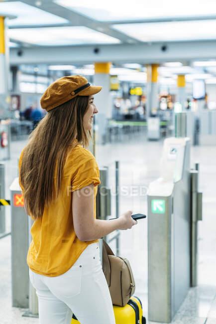 Жіночий пасажир у модному одязі стоїть поруч, щоб перевірити лічильник в аеропорту. — стокове фото