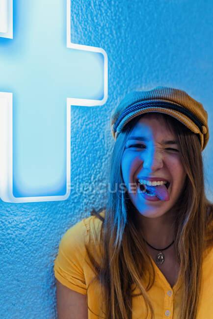 Felice giovane adolescente in t shirt gialla e berretto alla moda facendo smorfia divertente e mostrando la lingua contro il muro blu con neon segno di croce medica — Foto stock