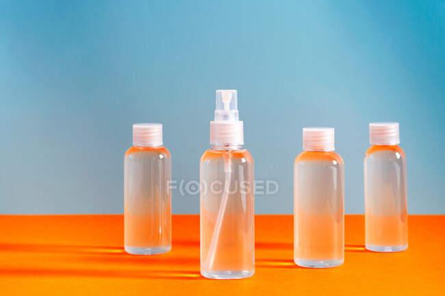 Verschiedene klare Flaschen mit Salzgel zur Desinfektion von covid-19 Händen über blauem und orangefarbenem Hintergrund — Stockfoto
