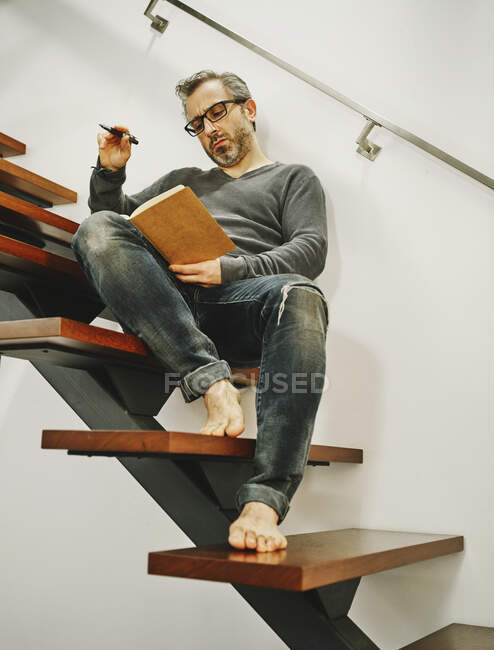 Low angle of mature man in eyeglasses relaxing with cup of coffee on wooden steps in contemporary apartment and writing plans in notebook — Stock Photo