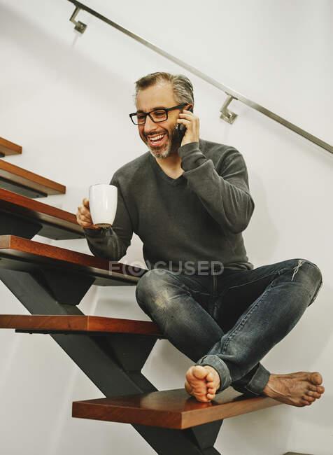 Homem rindo em roupas casuais sentado em escadas de madeira e conversando no telefone celular enquanto desfruta de bebida quente durante o descanso no apartamento moderno — Fotografia de Stock