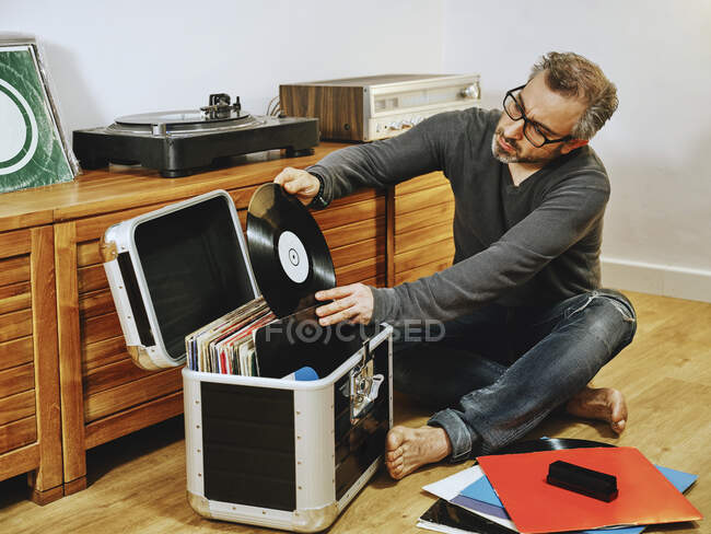 Stylish man wearing casual clothes and eyeglasses sitting on wooden floor and picking vinyl record while enjoying weekend at home — Stock Photo