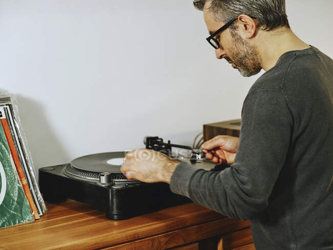 Side view of serious man setting turntable and enjoying songs on retro vinyl disc while chilling at home — Stock Photo