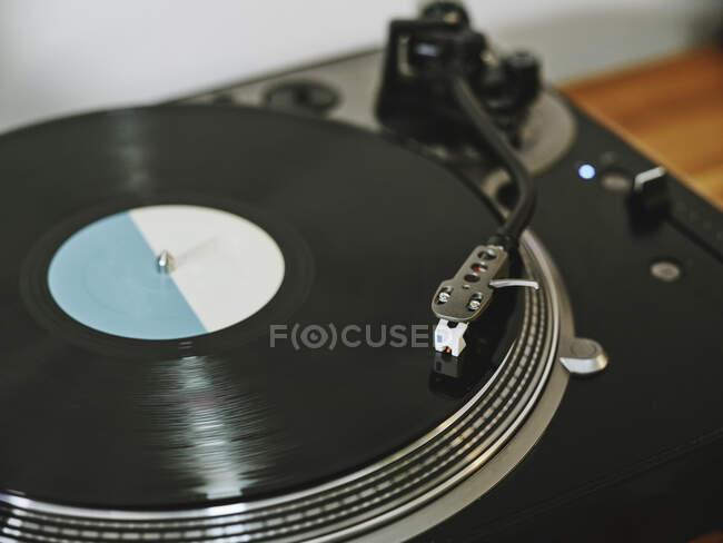 Dall'alto giradischi in vinile contemporaneo con disco retrò posto su tavolo in legno in salotto — Foto stock